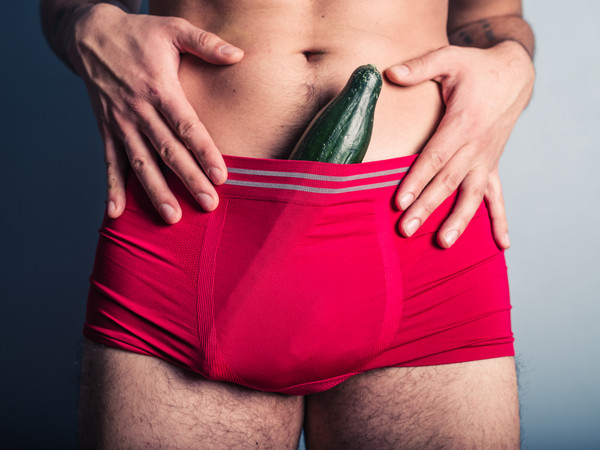 Young man with cucumber in his underpants